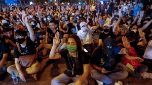 Pro-democracy protesters display three-fingered salute during a rally at a major intersection next to the German Embassy in central Bangkok, Thailand, on Oct. 26, 2020. (Gemunu Amarasinghe / AP)