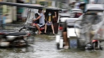 Residents wearing masks to prevent the spread of the coronavirus ride motorcycles as they negotiate a flooded road due to Typhoon Molave in Pampanga, Philippines, on Oct. 26, 2020. (Aaron Favila / AP)