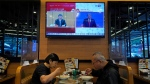 A TV screen broadcasts Chinese President Xi Jinping during a rally in Beijing, left, and U.S. President Donald Trump speaking at the presidential debate, right, at a restaurant in Hong Kong, on Oct. 23, 2020. (Kin Cheung / AP)
