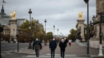 People wearing masks, walk in the Invalides district of Paris, on Oct.25, 2020. (Lewis Joly / AP)
