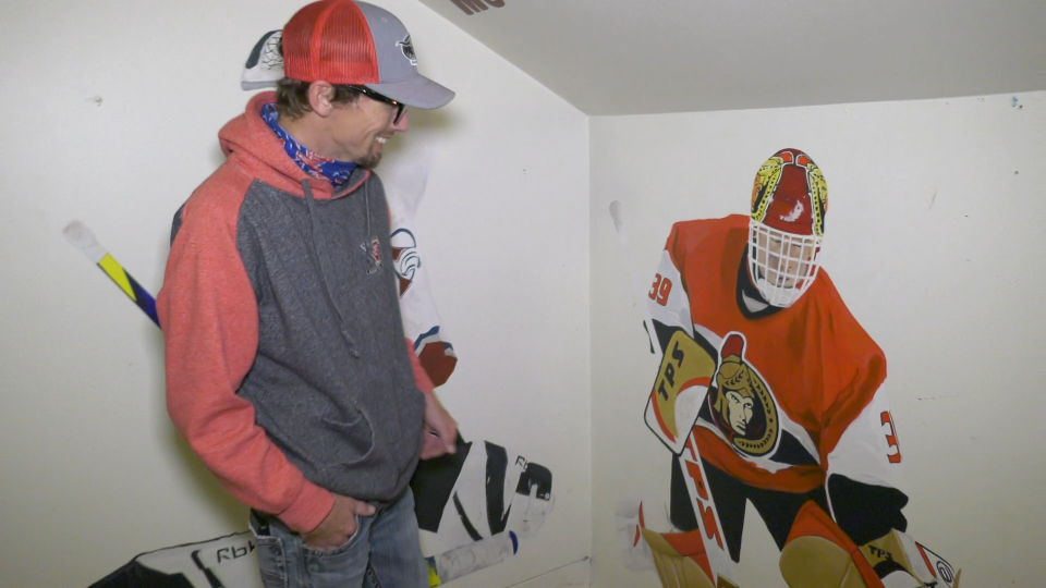 Garrett McCallum in his old bedroom, admiring the Dominik Hasek mural. (Nate Vandermeer / CTV News Ottawa)
