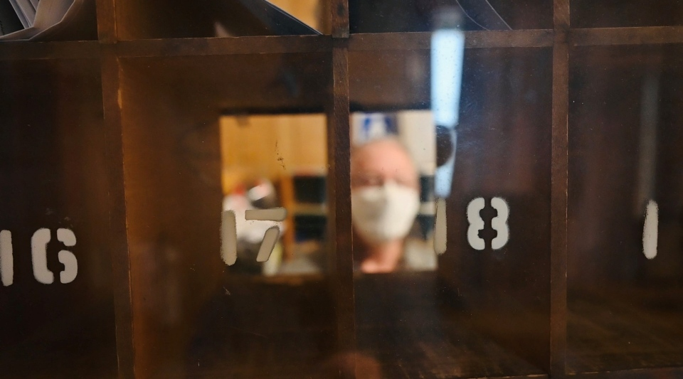 Ron Bickerton puts mail in the numbered boxes at the Edwards, Ont. Post Office, which is also his family's home. (Joel Haslam / CTV)