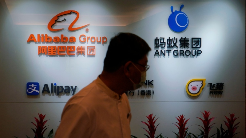 An employee walks past the logos of Ant Group and Alibaba Group at the Ant Group office in Hong Kong, on Oct. 23, 2020. (Kin Cheung / AP)
