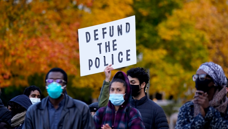 A person holds a sign calling for the defunding of the police during a rally after an Ottawa Police constable was found not guilty of manslaughter, aggravated assault and assault with a weapon in connection with the 2016 death of Abdirahman Abdi, a 37-year old Black man, in Ottawa, on Tuesday, Oct. 20, 2020. THE CANADIAN PRESS/Justin Tang
