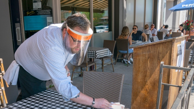 Charles Wood wipes down a table on the patio of Paradiso in Oakville, Ont., Saturday, June 20, 2020. THE CANADIAN PRESS/Frank Gunn