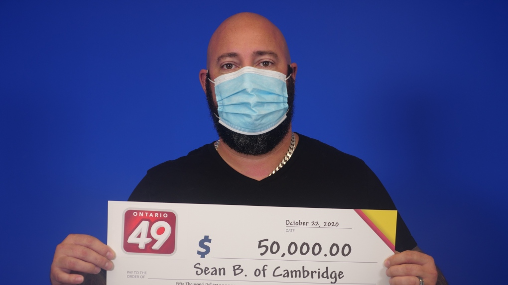 A man posing with a large OLG cheque
