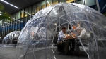 People enjoy outdoor dining in a weather proof dome pod at Against the Grain Urban Tavern during the COVID-19 pandemic in Toronto on Wednesday, October 21, 2020. THE CANADIAN PRESS/Nathan Denette
