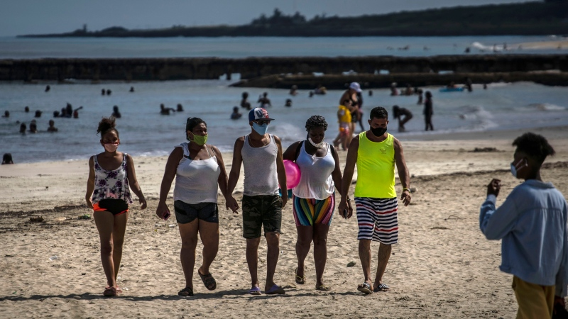 People wearing masks as a precaution against the spread of the new coronavirus walk from the beach in Havana, Cuba, Sunday, Oct. 11, 2020. (AP Photo/Ramon Espinosa)
