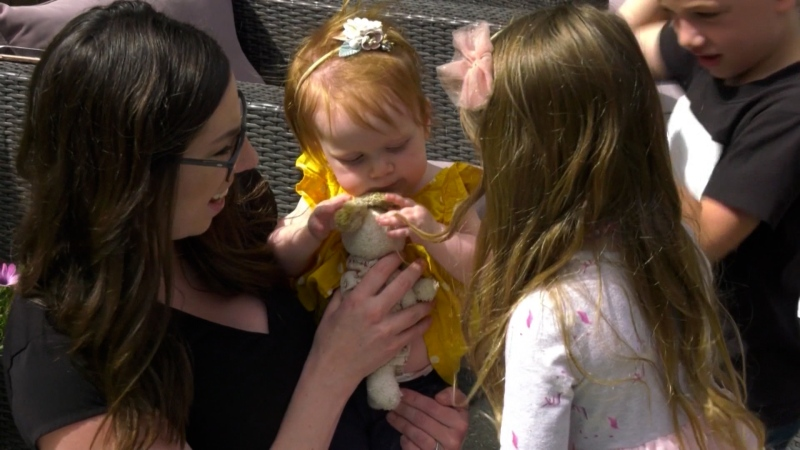 Harper Hanki, held by her mother in this file photo from July, was selected in a random lottery for a one-time drug treatment for a rare condition.