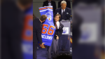 Wayne Gretzky and Joey Moss hold up a banner bearing Gretzky's number during a jersey retirement ceremony at Skyreach Centre on October 1, 1999. (CP PHOTO/Jeff McIntosh)