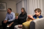 Saskatchewan NDP Leader Ryan Meili, left, sits beside wife Mahli Brindamour with their son Abraham, right, as they watch the provincial election results in their room at the Delta Marriott in Saskatoon, Sask., Monday, Oct. 26, 2020. THE CANADIAN PRESS/Kayle Neis