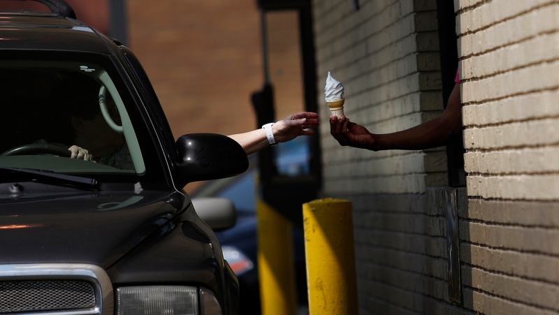 A driver receives a soft serve ice cream cone from an employee working the drive-thru at a McDonald's. (Luke Sharrett/Bloomberg/Getty Images/CNN)