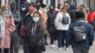 People wear face masks as they wait to enter a store in Montreal, Sunday, October 25, 2020, as the COVID-19 pandemic continues in Canada and around the world. THE CANADIAN PRESS/Graham Hughes
