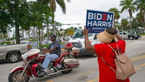 People campaigning at South Dade Regional Library as part of the Souls to the Polls one of many events prior to the elections on Sunday, Oct. 25, 2020, in Miami, Fla. (David Santiago/Miami Herald via AP)