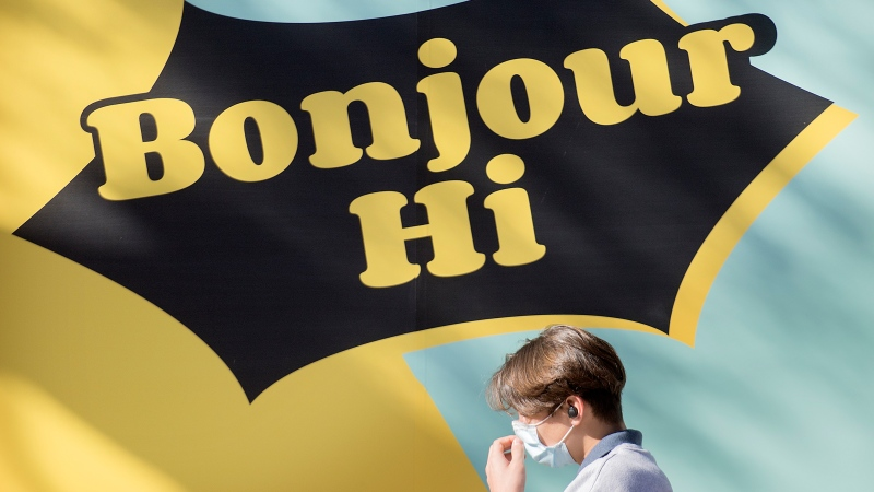 A man adjusts his face mask as he walks by a sign reading 'Bonjour, Hi' in Montreal, Sunday, October 25, 2020, as the COVID-19 pandemic continues in Canada and around the world. THE CANADIAN PRESS/Graham Hughes