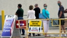 Voters are urged to maintain social distancing to avoid the spread of the coronavirus as they wait in line to cast their ballots outside the Polk County Government Center Monday, Oct. 19, 2020, in Lakeland, Fla. (AP Photo/Chris O'Meara)