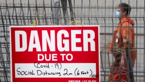 A construction sign on a fence surrounding an excavation indicates the danger is Covid-19 as a construction worker walks past Tuesday October 27, 2020 in Ottawa. (Adrian Wyld/THE CANADIAN PRESS)