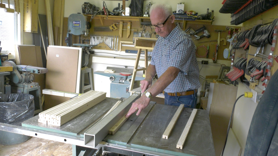 Roland Besner using a saw to groove wood to make desks for young students who are learning from home. (Nate Vandermeer / CTV News Ottawa)