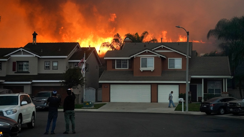 Residents watch as the Blue Ridge Fire burns along the hillside Tuesday, Oct. 27, 2020, in Chino Hills, Calif. (AP Photo/Jae C. Hong)