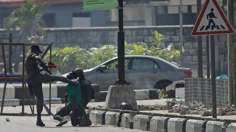 In this Oct. 21, 2020 file photo, police officers detain a protester at the Lekki toll gate in Lagos, Nigeria.  (Sunday Alamba / AP)