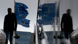 A man carries a cycling helmet as he walks by EU flags outside EU headquarters in Brussels, on Oct. 28, 2020. (Virginia Mayo / AP)