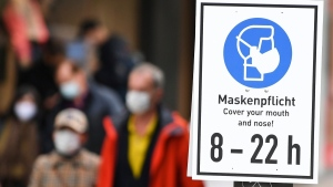 A sign with the inscription 'Masks Required. Cover your mouth and nose! 8 - 22 h' is displayed in Frankfurt, Germany, on Oct. 28, 2020. (Arne Dedert / dpa via AP)