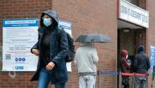 A man walks past the lineup for COVID-19 Assessments at Toronto Western Hospital in Toronto on Tuesday October 27, 2020. The hospital has declared a COVID-19 outbreak and has closed some wards. THE CANADIAN PRESS/Frank Gunn