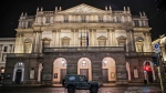 """In this early Sunday, Oct. 25, 2020 file photo, A military vehicle drives past La Scala opera theater in Milan, northern Italy. The number of performers at Milan's famed La Scala opera house positive with the coronavirus has risen to 21, even as the theater was forced to close due to new government restrictions aimed at curbing the virus' resurgence. La Scala spokesman Paolo Besana confirmed Tuesday that 18 members of the world-class chorus and three woodwind players in the orchestra have the virus. That comes after two singers, including tenor Francesco Meli, tested positive, ahead of planned concert performances last week of """"Aida.''(AP Photo/Luca Bruno, File)"""