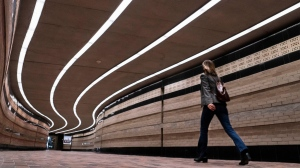 A woman walks through an empty underground tunnel linking office buildings in Montreal, on Wednesday, Oct. 14, 2020. THE CANADIAN PRESS/Paul Chiasson