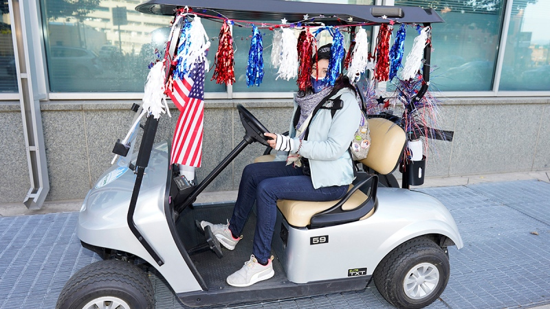 Tibby Starks, a worker for the Denver Election Division, rolls up in a golf cart adorned with patriotic poms and an American flag before a news conference on the process of casting a vote in the upcoming general election Thursday, Oct. 15, 2020, in downtown Denver. (AP Photo/David Zalubowski)