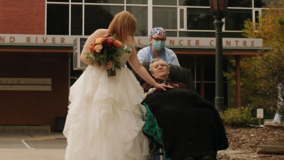A bride walks with her father on a ventilator