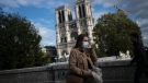 A woman walks by Notre Dame cathedral Saturday Sept.26, 2020 in Paris. While France suffered testing shortages early in the pandemic, ramped-up testing since this summer has helped authorities track a rising tide of infections across the country. More than 15,000 new cases were reported Friday, and the Paris hospital system is starting to delay some non-virus surgeries to free up space for COVID-19 patients. (AP / Lewis Joly)