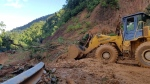 A bulldozer clears out the road damaged by landslide to access a village swamped by another landslide in Quang Nam province, Vietnam on Thursday, Oct. 29, 2020. (Bui Van Lanh/VNA via AP)