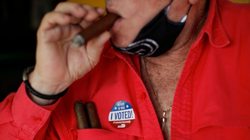 "Ramon Silva, 78, wears an ""I voted"" sticker, as he smokes a cigar in Little Havana, after casting his ballot in early voting in Miami, Wednesday, Oct. 28, 2020. (AP Photo/Rebecca Blackwell)"