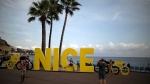 Tourists pose for pictures with an installation set up for the start of the 107th Tour de France cycling race in Nice, southern France, Friday, Aug 28, 2020. (AP Photo/Daniel Cole)