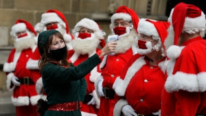 Santas have their temperature taken as they attend a socially distanced Santa school training at Southwark Cahedral in London, Monday, Aug. 24, 2020. (AP Photo/Kirsty Wigglesworth)