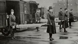 The St. Louis Red Cross Motor Corps was on duty with mask-wearing women holding stretchers at the backs of ambulances during the influenza epidemic in Missouri in October 1918. (U.S. Library of Congress)