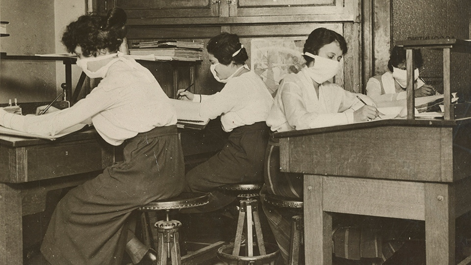 Female clerks in New York work with masks tied around their faces on Oct. 16, 1918. (U.S. National Archives)