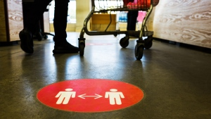 A physical distancing decal seen on the floor of a store. (Shutterstock)