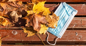 Face mask on bench with fall leaves