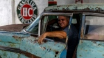 Julio Alvarez, co-owner of Nostalgicar, poses inside his latest classic American car acquisition that he hopes to restore in Havana, Cuba, Wednesday, Oct. 21, 2020. (AP Photo/Ramon Espinosa)