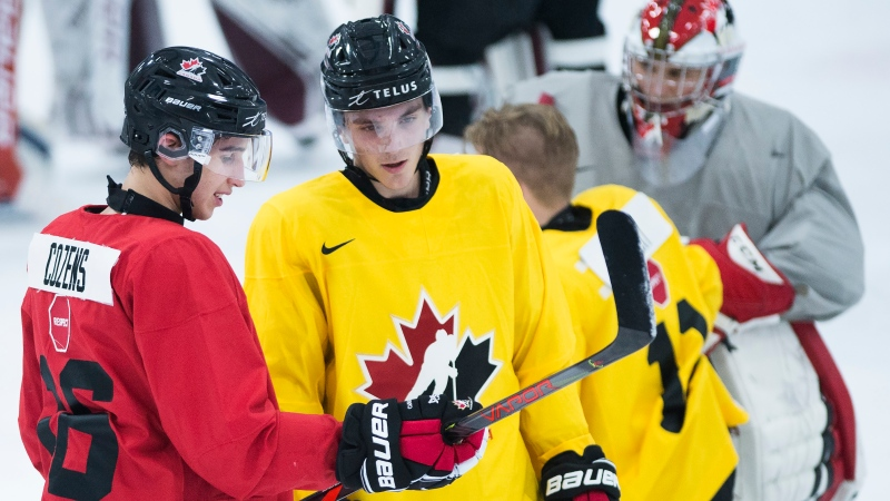 Dylan Cozens, left, talks with Peyton Krebs, right, during practice at Team Canada's selection camp in 2019. Both players have a chance to return to the team for this year's tournament. (THE CANADIAN PRESS/Nathan Denette)