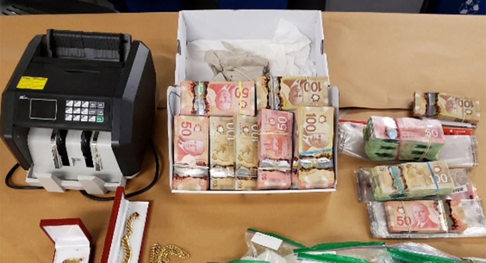 Cash and a money counter seized by police in London, Ont. on Wednesday, Oct. 28, 2020 are seen in this image released by the London Police Service.