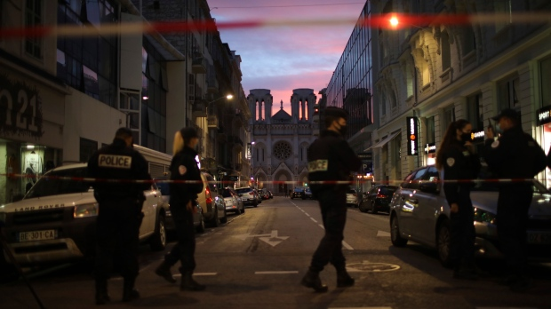 Police work behind a restricted zone near the Notre Dame church in Nice, southern France, after a knife attack took place on Thursday, Oct. 29, 2020. (AP Photo/Daniel Cole)