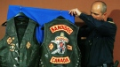 An OPP officer places biker vests seized in raids on display prior to a news conference in London, Ont., Monday April 10, 2006. (CP PHOTO/Adrian Wyld)