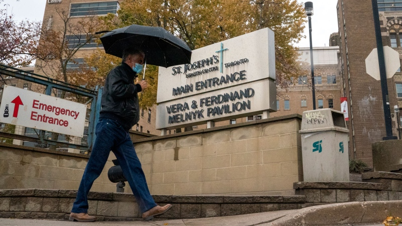 A man walks into the main entrance to St Joseph's Health Centre in Toronto, Monday, Oct. 19, 2020. The hospital has declared an outbreak of COVID-19. THECANADIAN PRESS/Frank Gunn