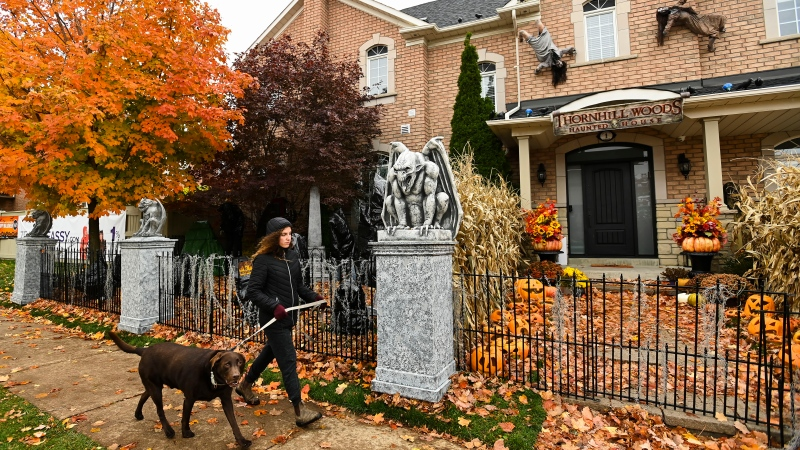 A woman walks her dog past the Thornhill Woods Halloween haunted house during the COVID-19 pandemic in Thornhill, Ont., on Monday, October 19, 2020. (THE CANADIAN PRESS/Nathan Denette)