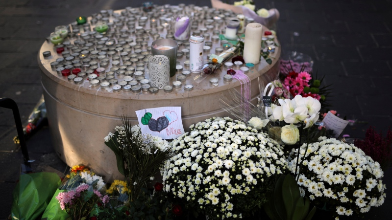 Flowers, messages and candles lie in front of the Notre Dame church, in Nice, France, Friday, Oct. 30, 2020. (AP Photo/Daniel Cole)