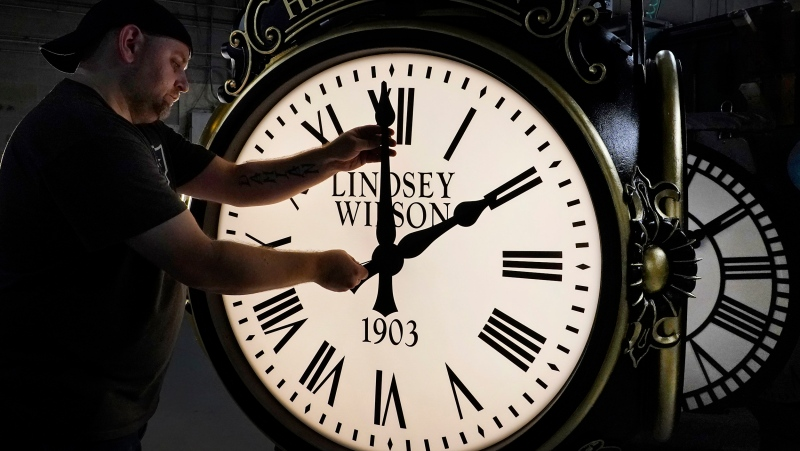 Dan LaMoore adjusts the hands on a Seth Thomas Post Clock at Electric Time Company, Friday, Oct. 23, 2020, in Medfield, Mass. (AP Photo/Elise Amendola)