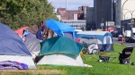 A man stands among tents at a homeless camp along a busy boulevard in Montreal, on Thursday, October 8, 2020. Many homeless people worry that being confined to a shelter will make them more likely to get COVID-19. THE CANADIAN PRESS/Paul Chiasson